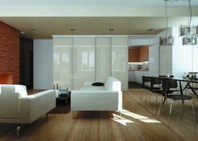 A világos nappali és a sötétebb színvilágú étkező egy fehér kanapéval van két részre osztva.